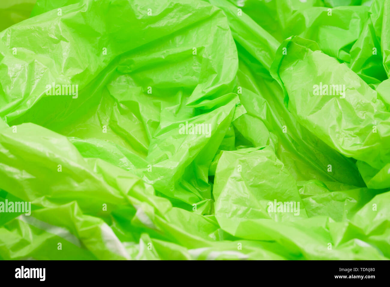 Green Plastic Bag Texture. Abstract Wrinkled Background of Plastic Garbage - Stock Image