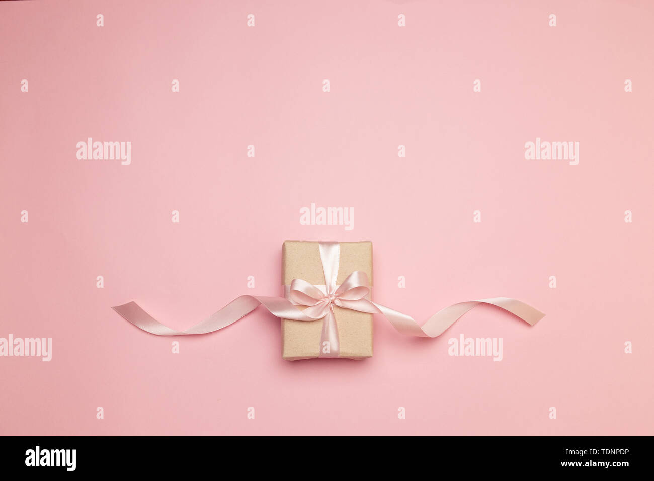 Minimalism concept. Holiday banner. Flat lay top view crafting paper gift on pink background. - Stock Image