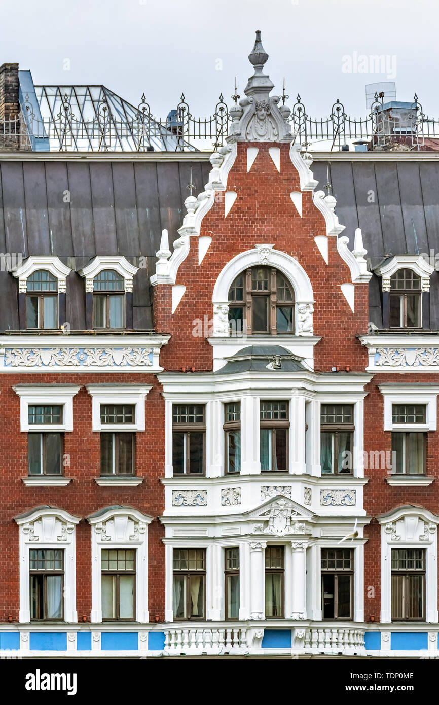 The facade of an old red brick building with white stucco windows and balconies in the old part of Riga. Stock Photo