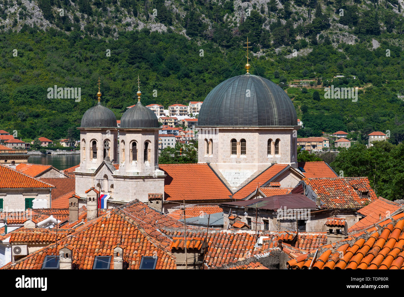 Serbian Orthodox Church of St. Nikola and Red tiled roofs of the old town houses in Kotor, Montenegro - Stock Image