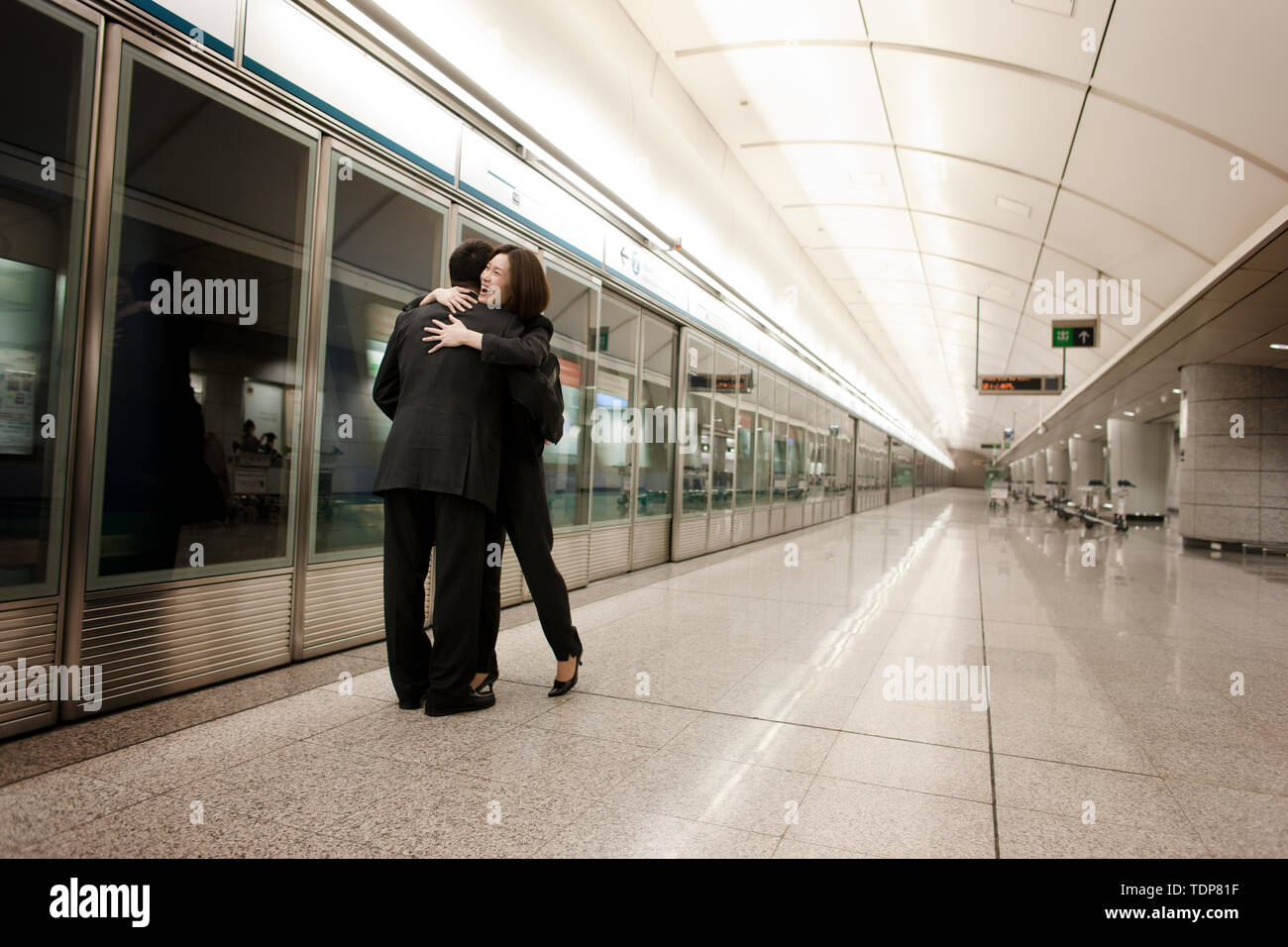 Couple greeting each other with a hug on the subway. - Stock Image