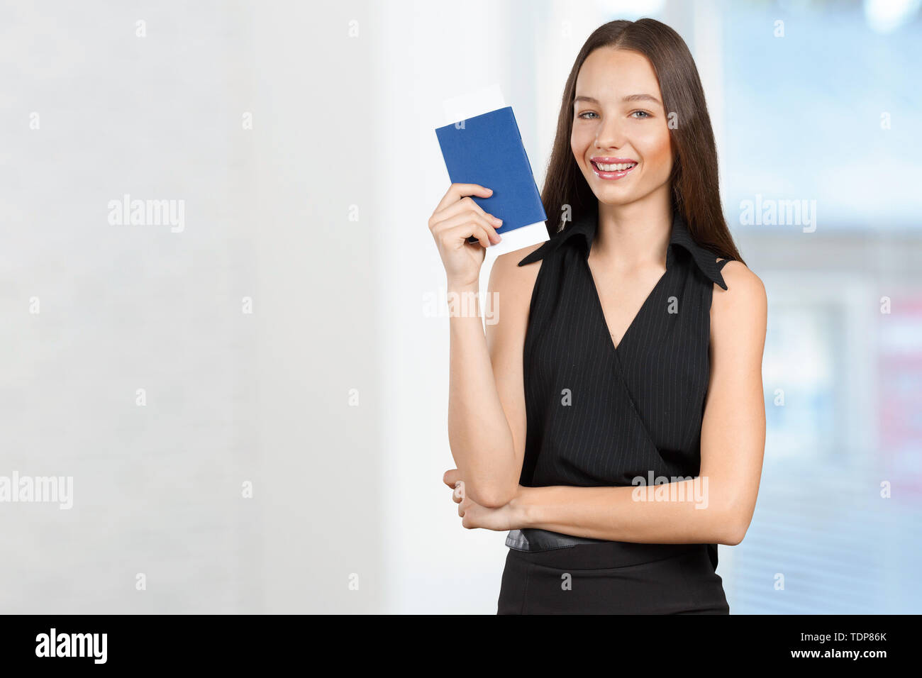 Portrait of happy tourist woman holding passport - Stock Image