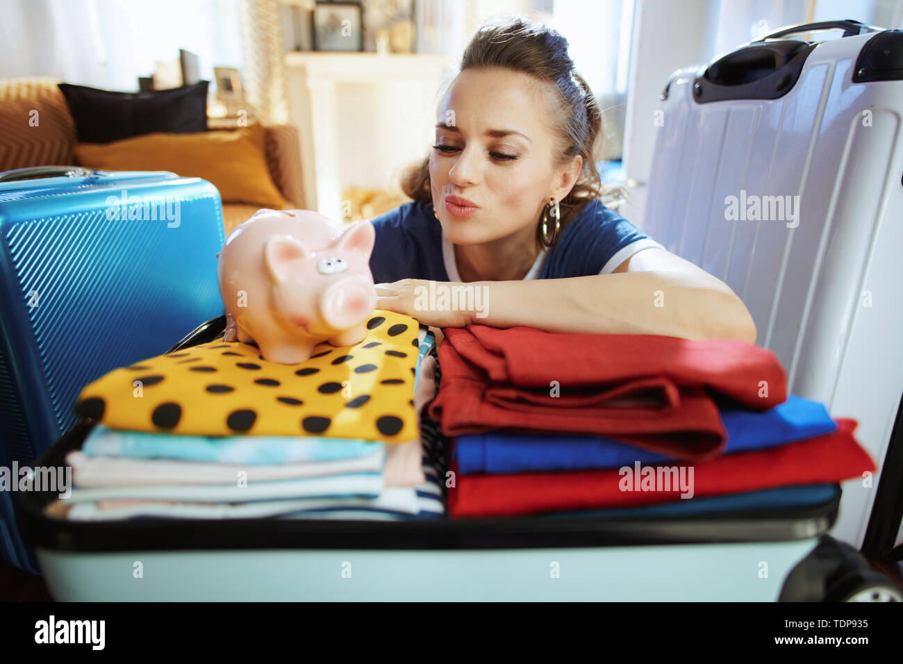 smiling modern woman in blue t-shirt at modern home in sunny summer day with piggy bank saved money on trip. - Stock Image