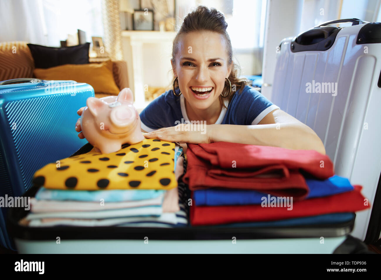 happy modern tourist woman in blue t-shirt with piggy bank planning budget tourism in the modern house in sunny summer day. - Stock Image