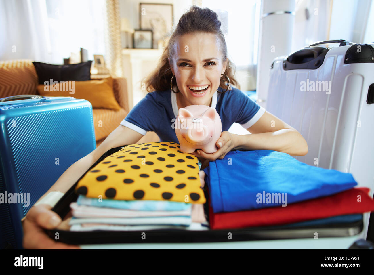 smiling modern tourist woman in blue t-shirt with piggy bank planning low cost travel at modern home in sunny summer day. - Stock Image