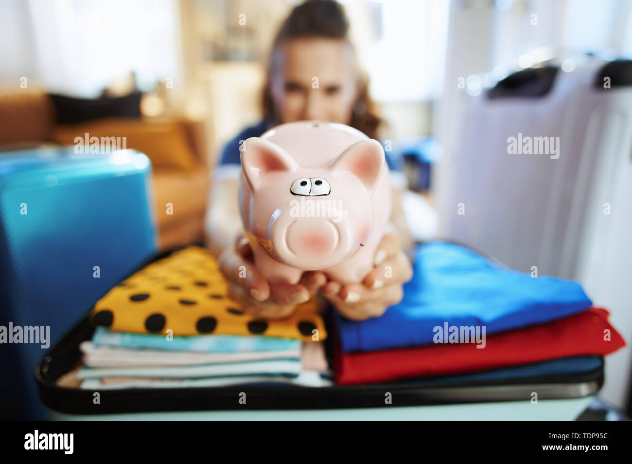 Closeup on elegant woman in blue t-shirt in the modern living room in sunny summer day showing piggybank. - Stock Image