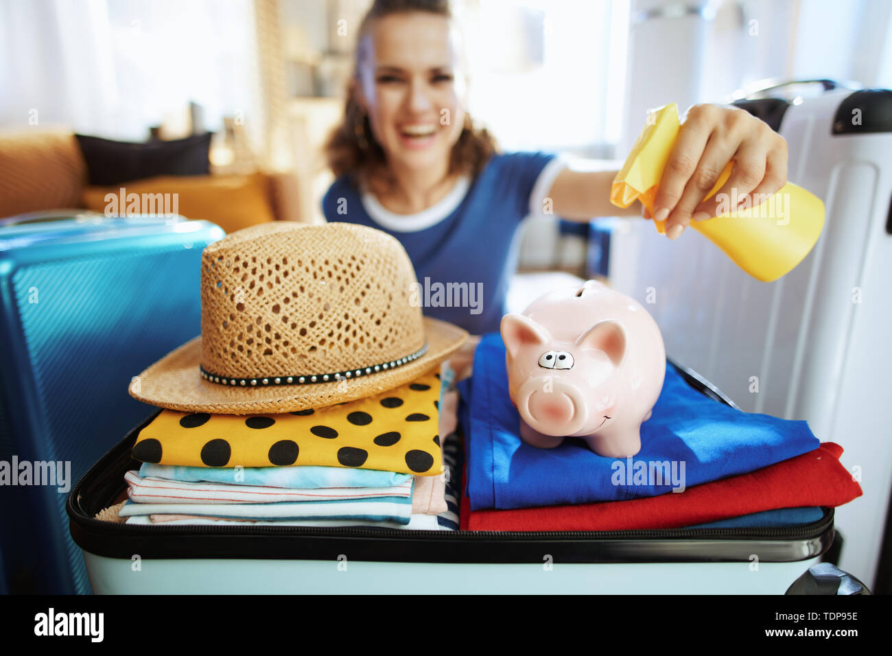 Closeup on cheerful stylish traveller woman in blue t-shirt at modern home in sunny summer day applying sunscreen on piggy bank. - Stock Image