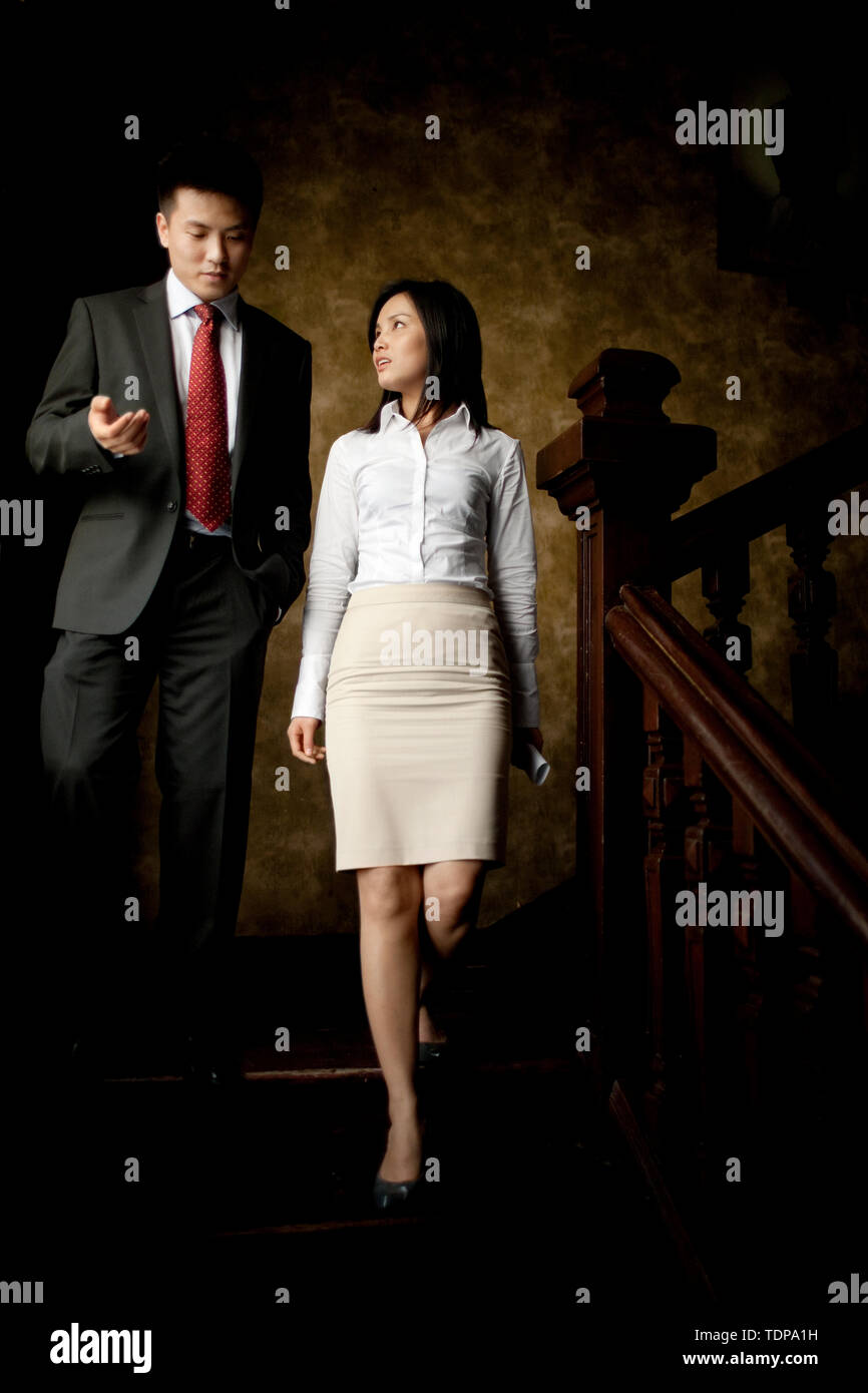 Two business professionals having a conversation while walking down a staircase. - Stock Image