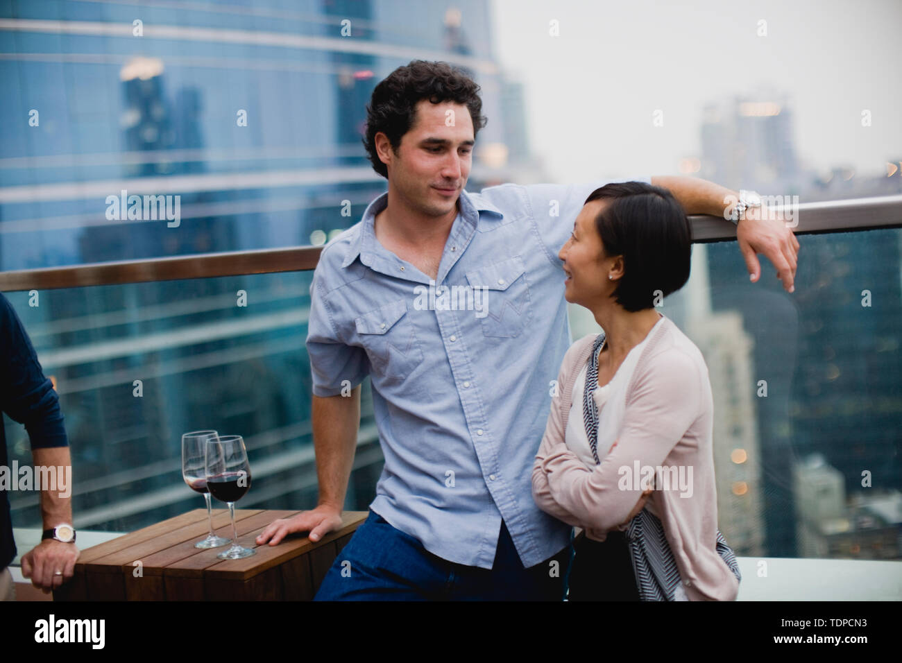 Young man talking with a young woman next to a railing in a rooftop bar in the city. - Stock Image