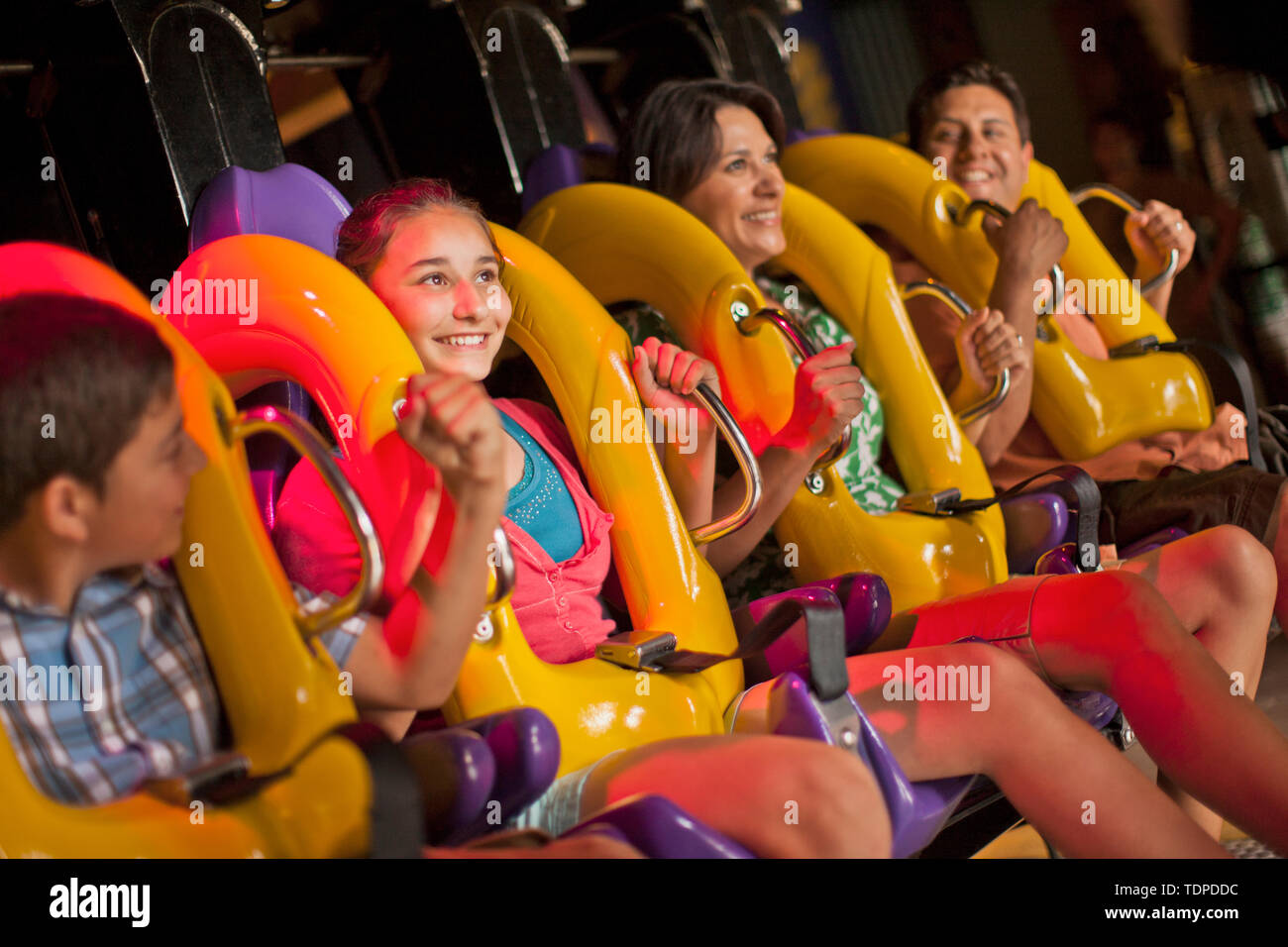 Smiling family preparing to go on a ride at an amusement park. - Stock Image