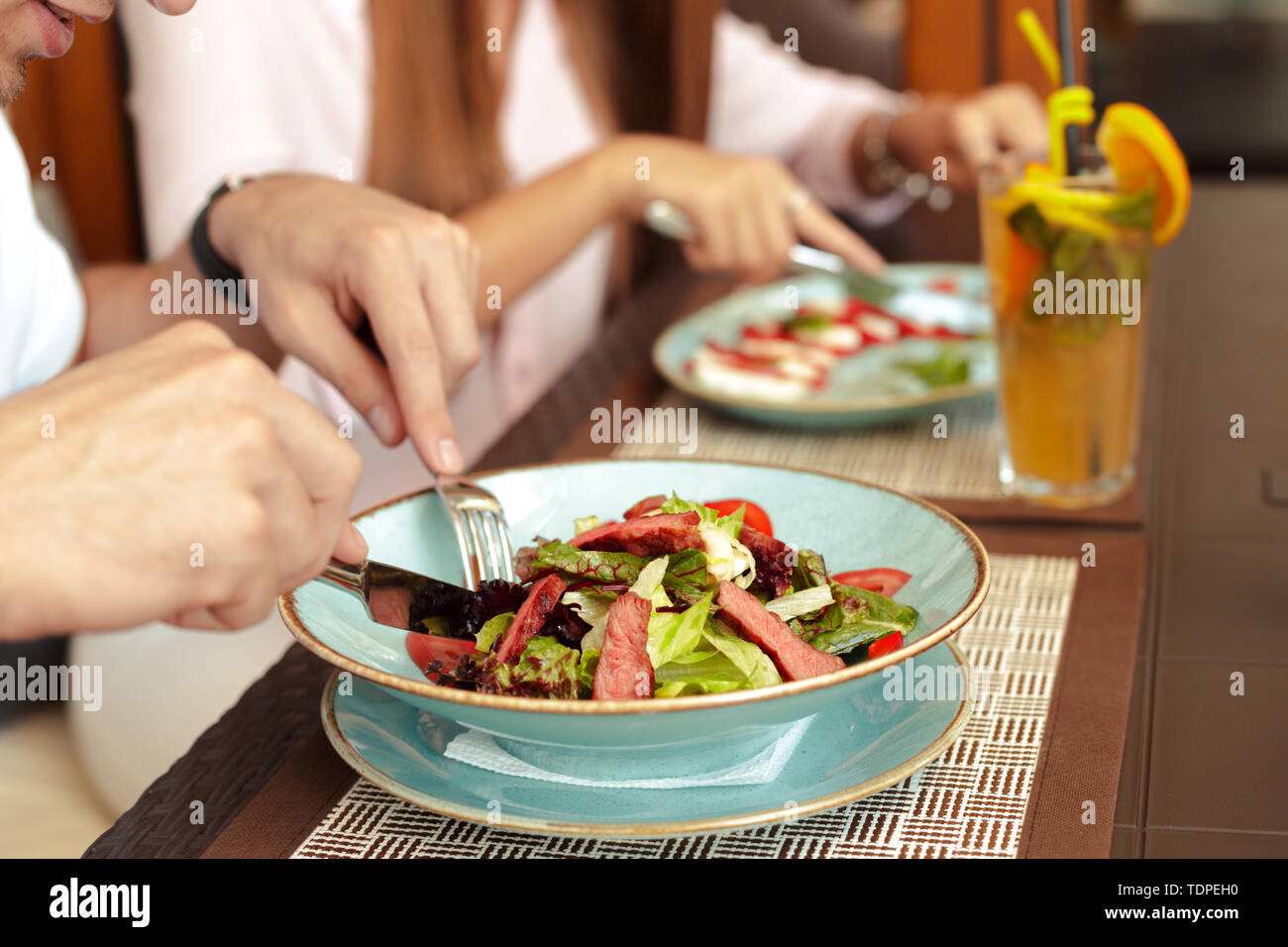 Happy loving couple enjoying breakfast in a cafe. - Stock Image