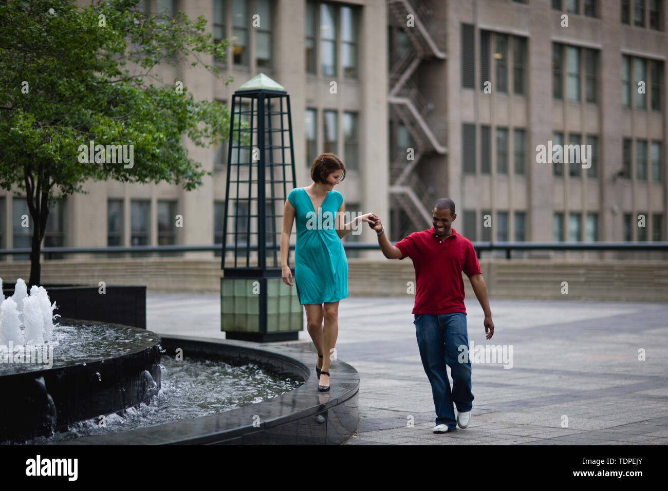 Happy young couple holding hands while walking next to a fountain in the city. - Stock Image