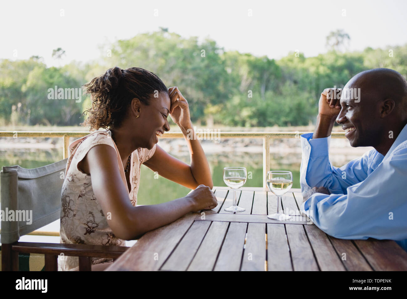 Happy mid-adult couple seated at an outdoor table. - Stock Image