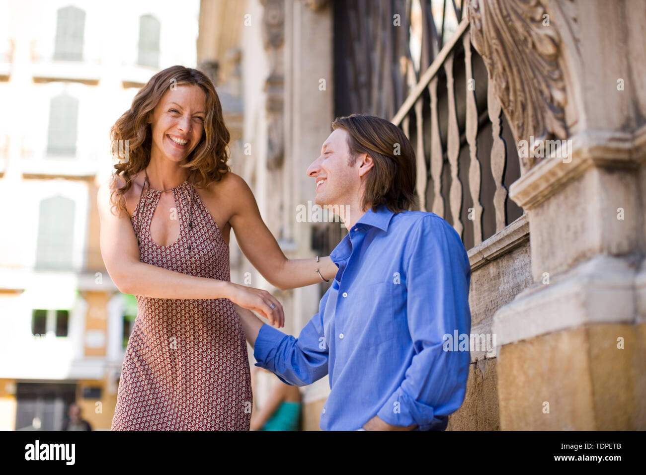 Mid-adult couple standing touching on a street. - Stock Image
