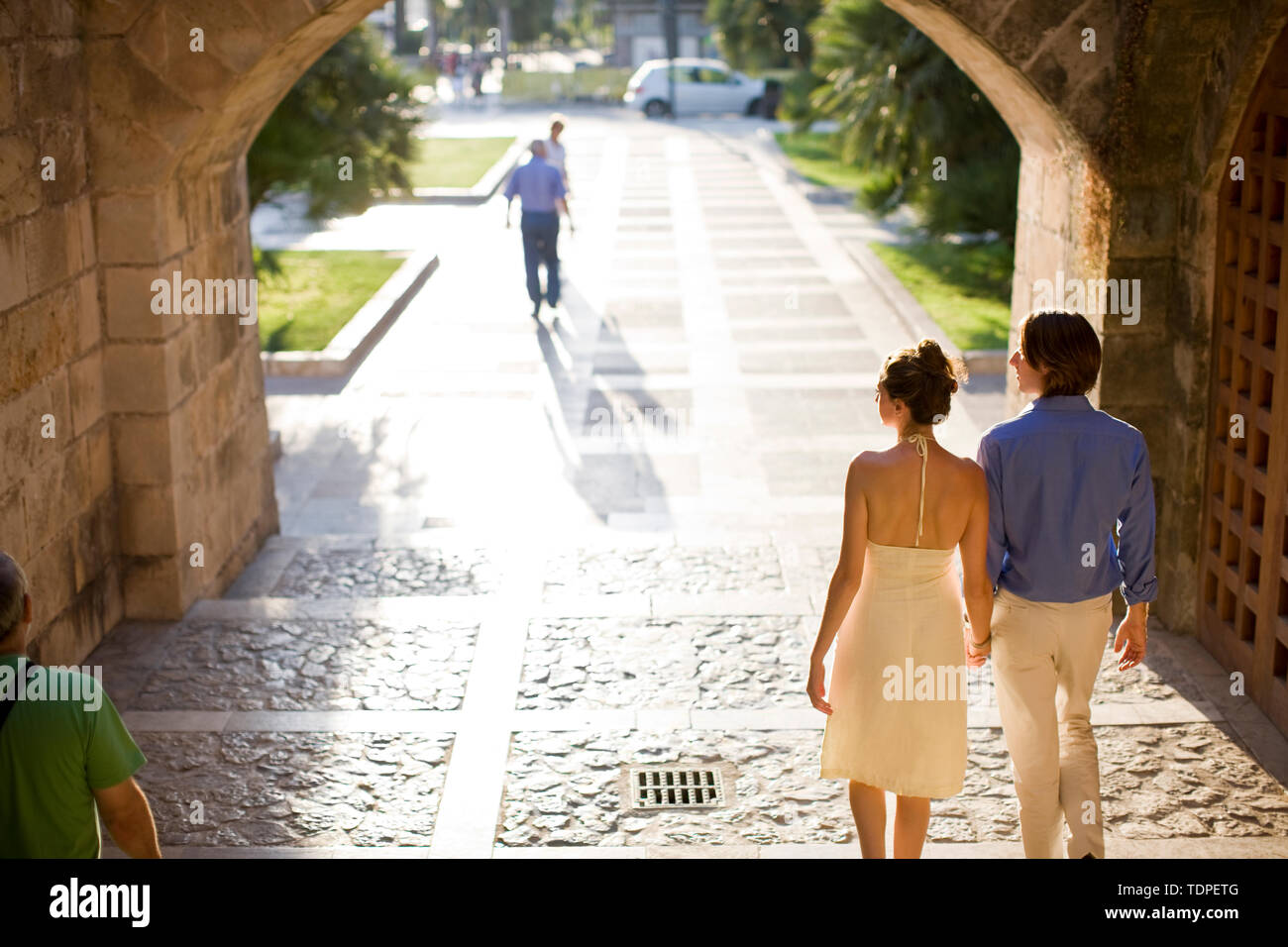 Couple walking into a park at sunset. - Stock Image