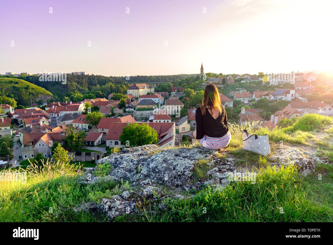 The green hill garden in the middle of old town Veszprem, Hungary with a woman sitting on the cliff enjoying the view Stock Photo