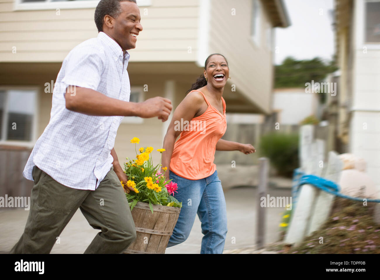 Couple carrying planter of flowers - Stock Image