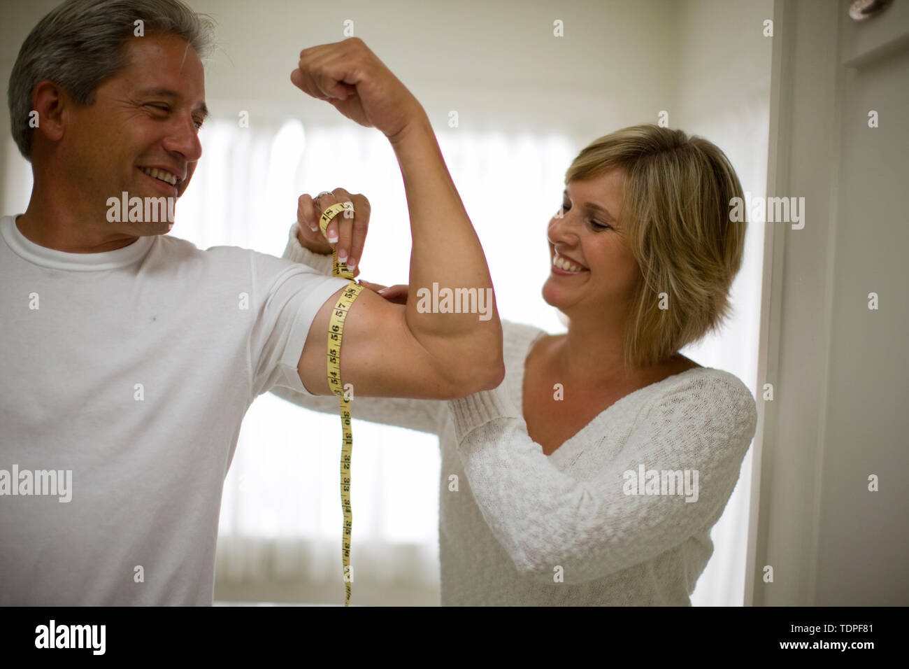 Smiling mid-adult woman measuring her husband's tricep muscle with a tape measure inside their home. - Stock Image