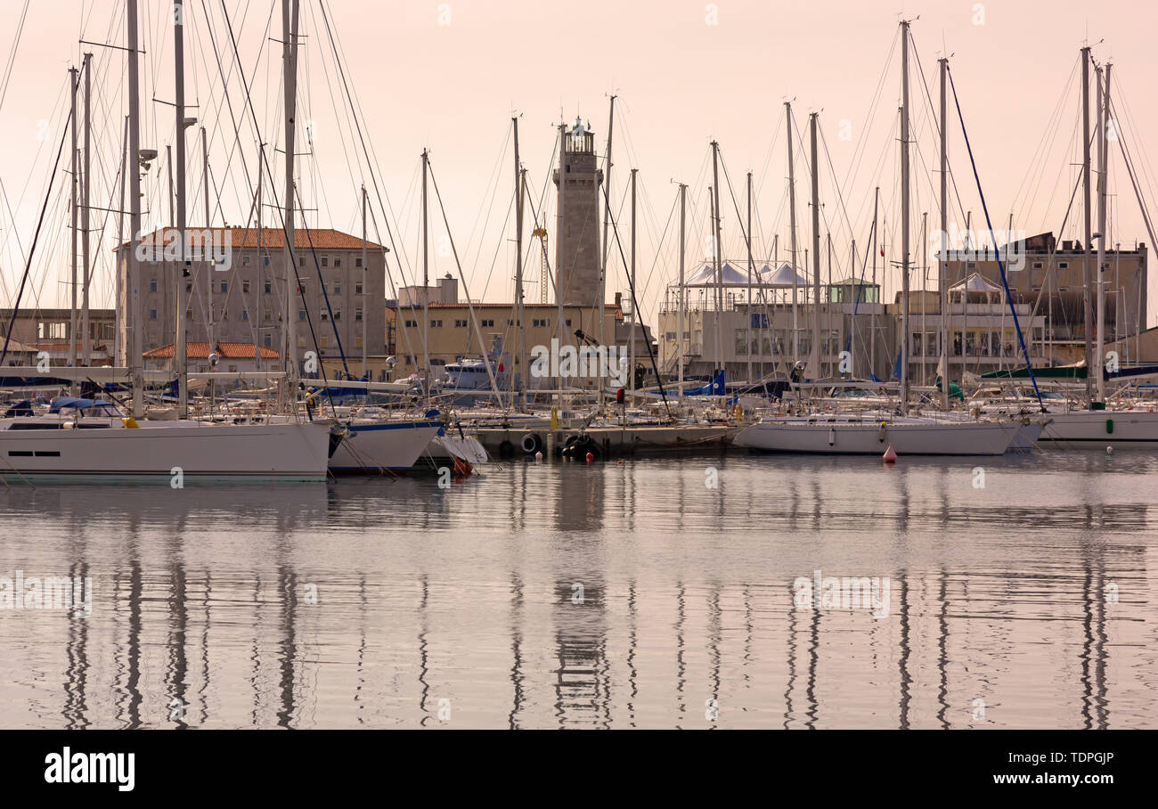 View of the Sacchetta marina at sunset, with the former Lanterna lighthouse in the background, in Trieste, Italy - Stock Image