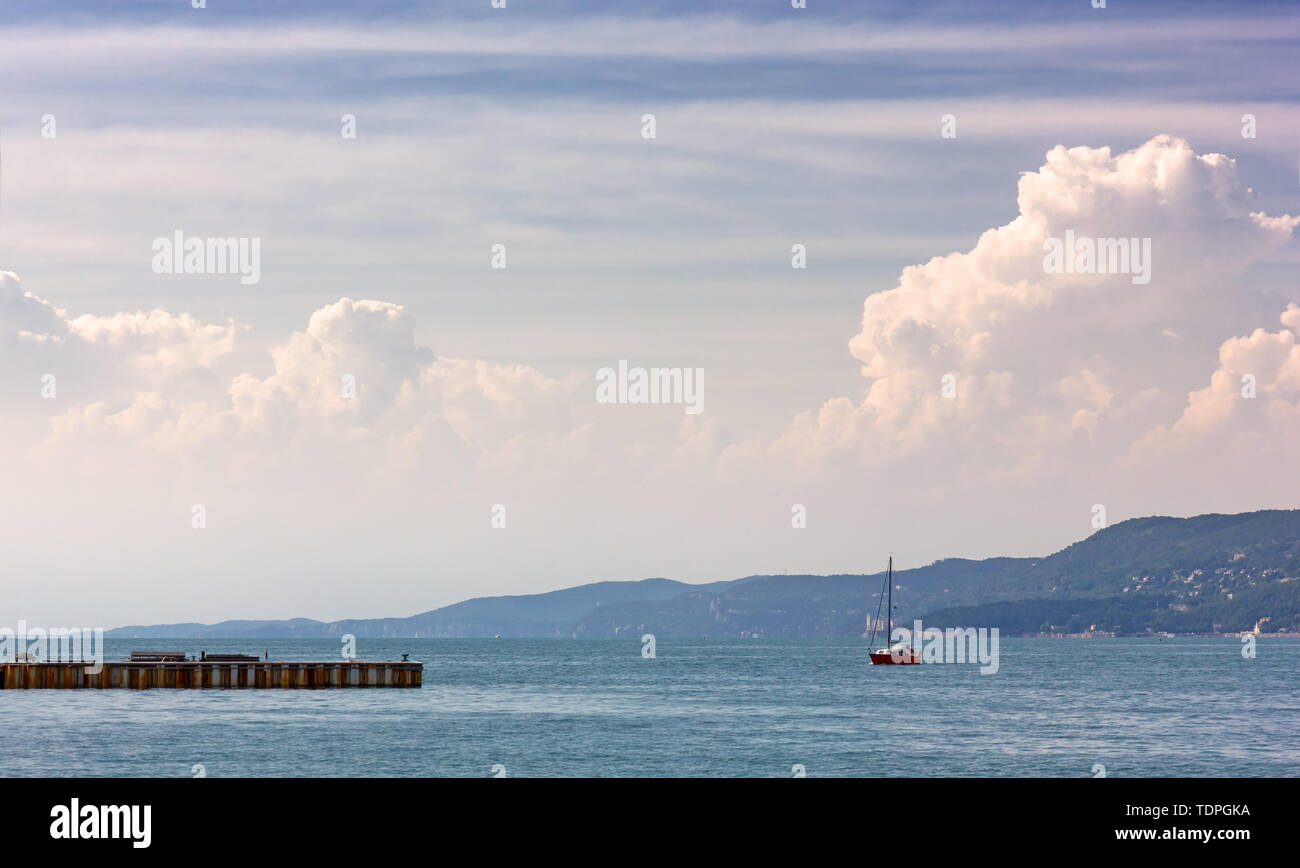 A red colored sailboat in the sea of Trieste, Italy, with the Miramare castle in the background - Stock Image