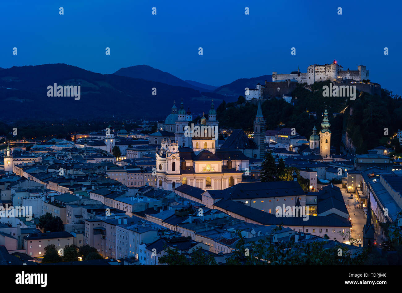 Salzburg Cityscape at Sunset, with Salzburg Cathedral and Hochensalzburg Fortress on top of the Hill. Photo was taken in summer Stock Photo