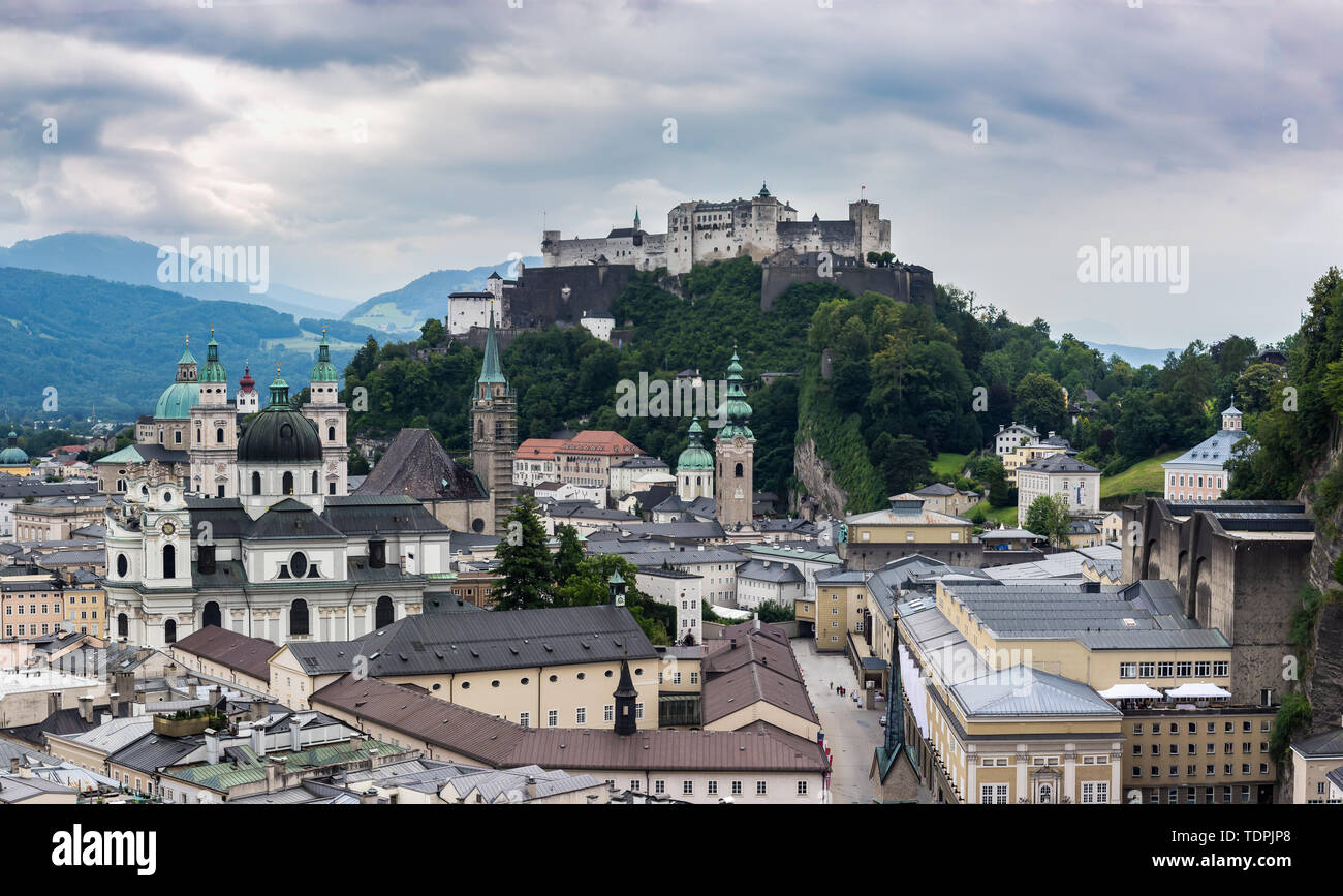 Salzburg Cityscape with Salzburg Cathedral and Hochensalzburg Fortress on top of the Hill. Photo was taken in summer Stock Photo