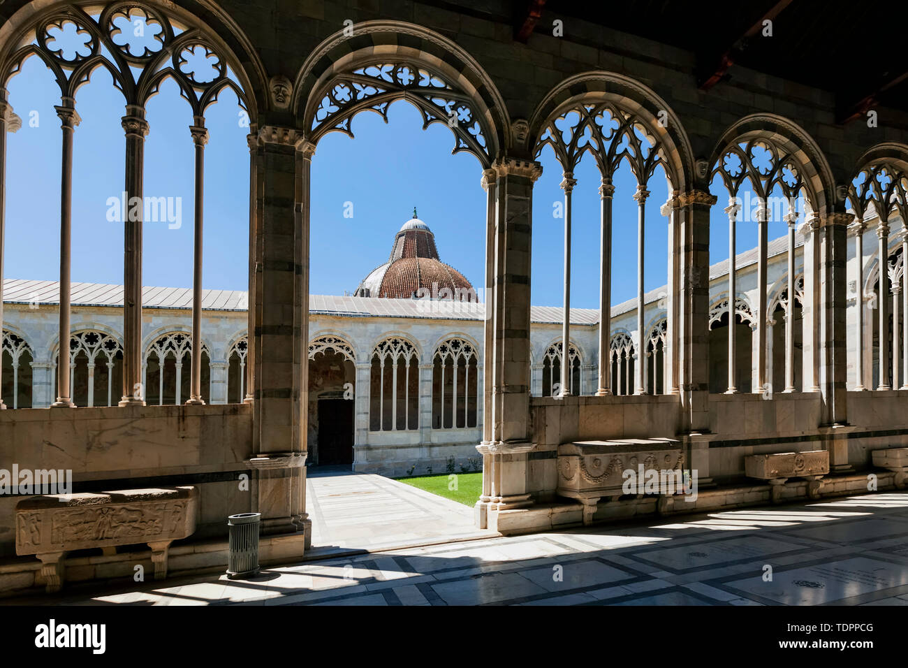 View of the Baptistry through the arches of Camposanto Monumentale (Campo Santo, Monumental Cemetery); Pisa, Italy Stock Photo