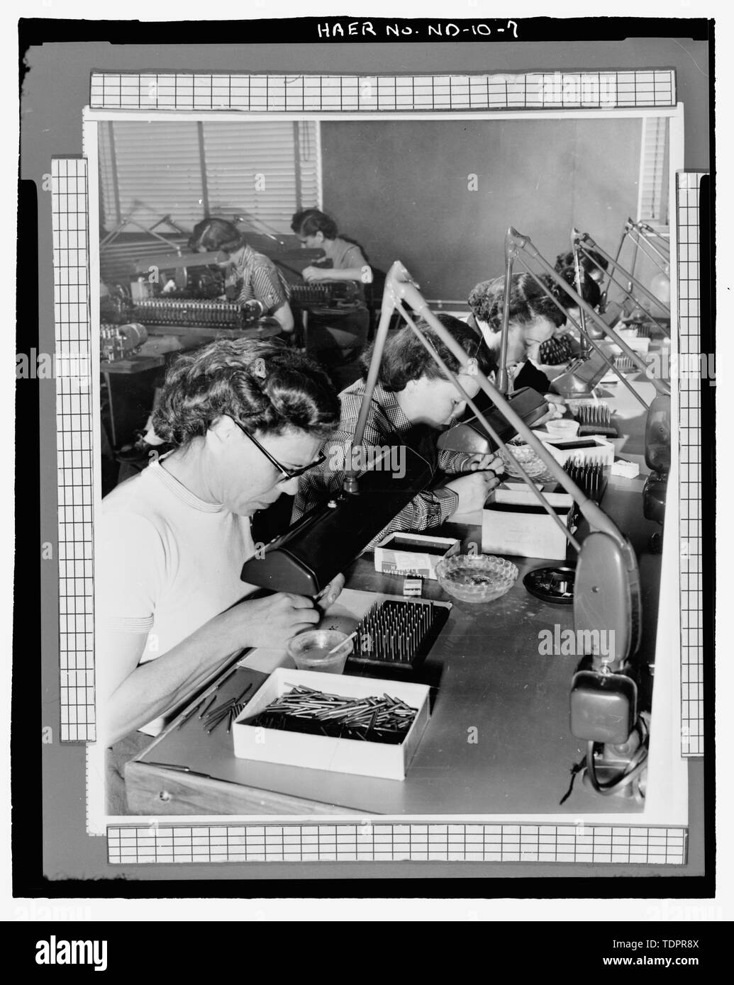 Photographic copy of photograph (original print in possession of William Langer Jewel Bearing Plant, Rolla, North Dakota). PASTING JEWEL BLANKS, PREPARATION FOR DRILLING. - Turtle Mountain Ordnance Plant, 213 First Street Northwest, Rolla, Rolette County, ND - Stock Image