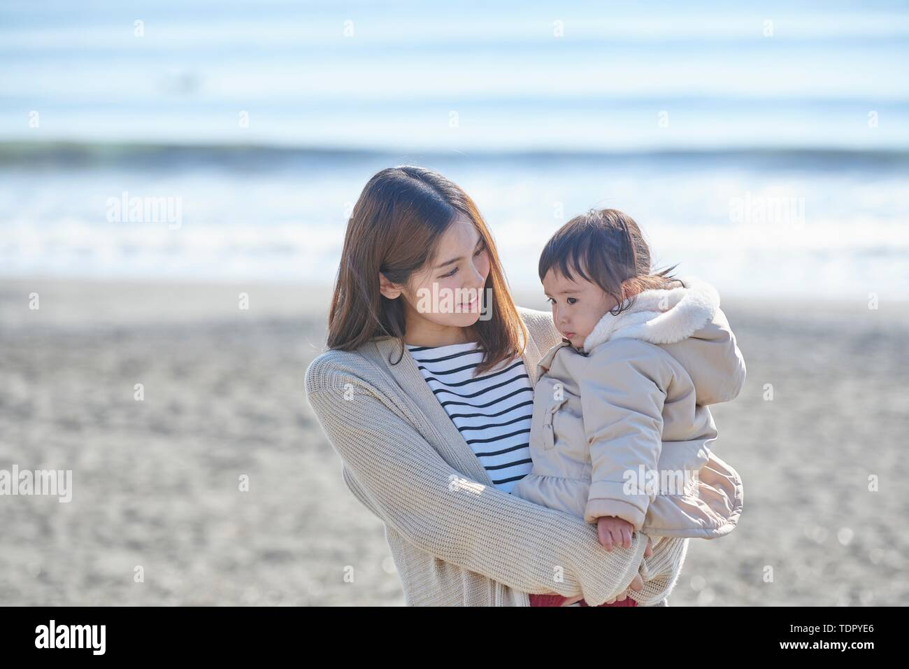 Japanese kid with mother at the beach - Stock Image