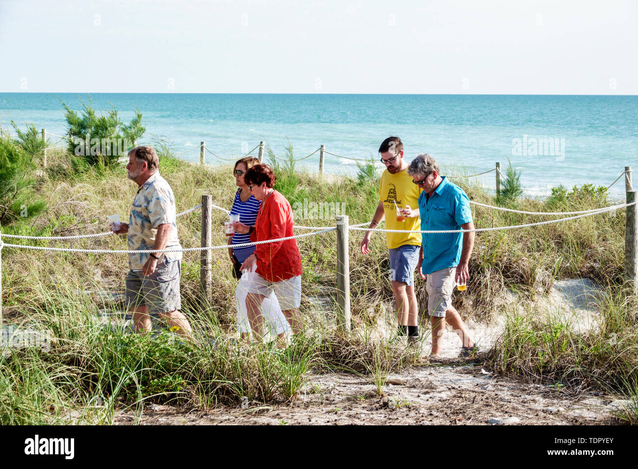 Captiva Island Florida Gulf of Mexico beach access pathway roped sand turquoise water man woman walking carrying drinks cups dune grasses couples friends - Stock Image
