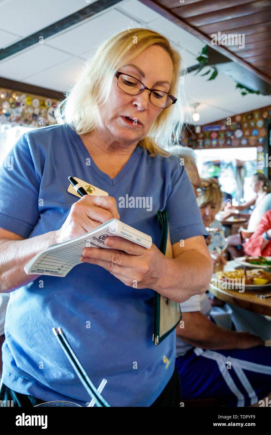 Captiva Island Florida The Mucky Duck restaurant inside woman waitress writing food order Stock Photo