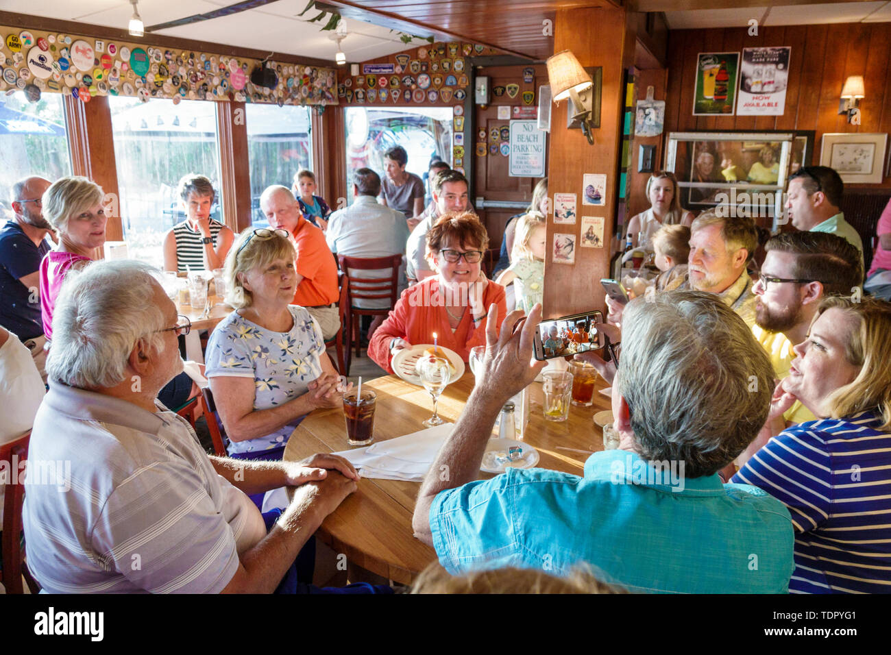 Captiva Island Florida The Mucky Duck restaurant inside tables crowded busy casual dining man woman birthday celebration taking photo smartphone Stock Photo