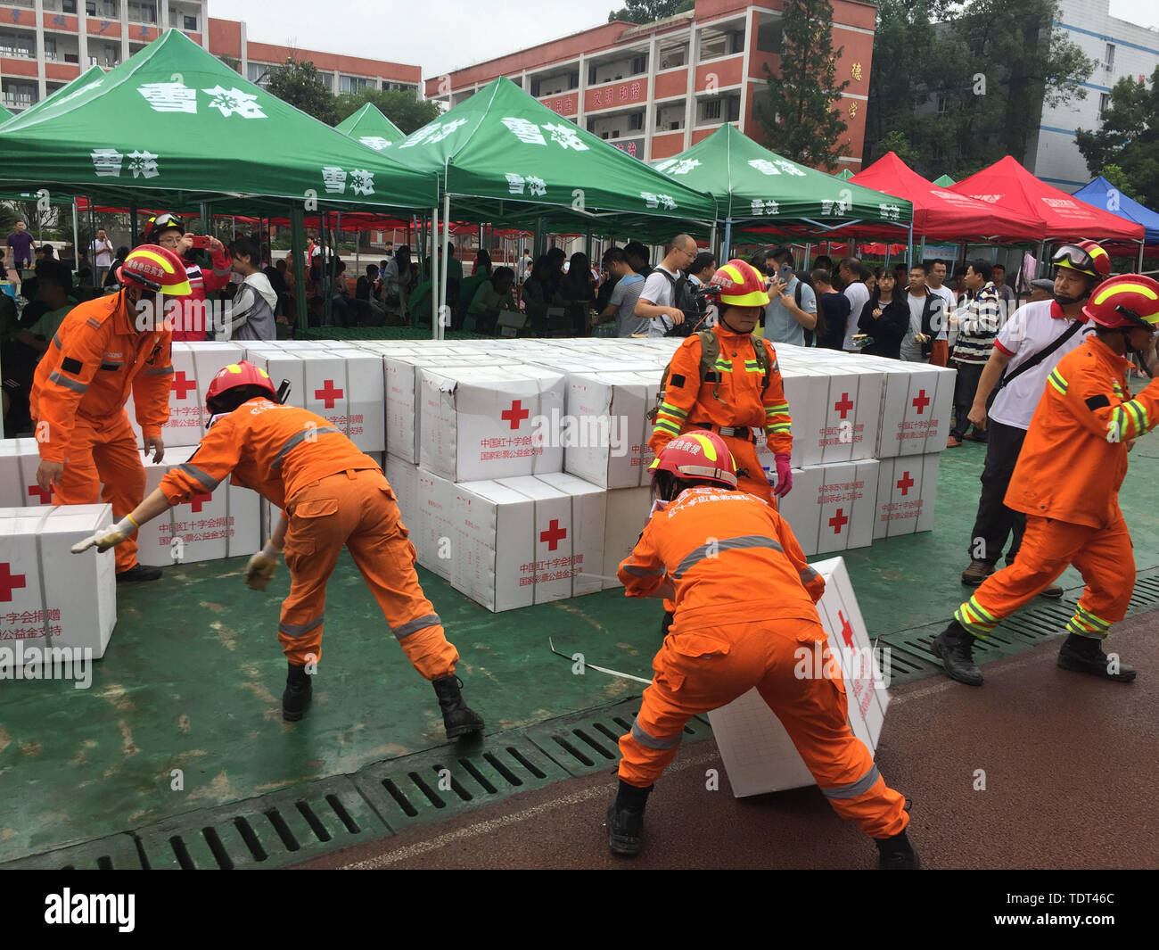 Changning. 18th June, 2019. Rescue workers handle relief materials at a temporary shelter at Shuanghe Town High School in Changning County of Yibin City, southwest China's Sichuan Province, June 18, 2019. Thirteen people died and 199 were injured after a 6.0-magnitude earthquake hit southwest China's Sichuan Province at 10:55 p.m. Monday, the Ministry of Emergency Management said Tuesday. Credit: Xinhua/Alamy Live News - Stock Image
