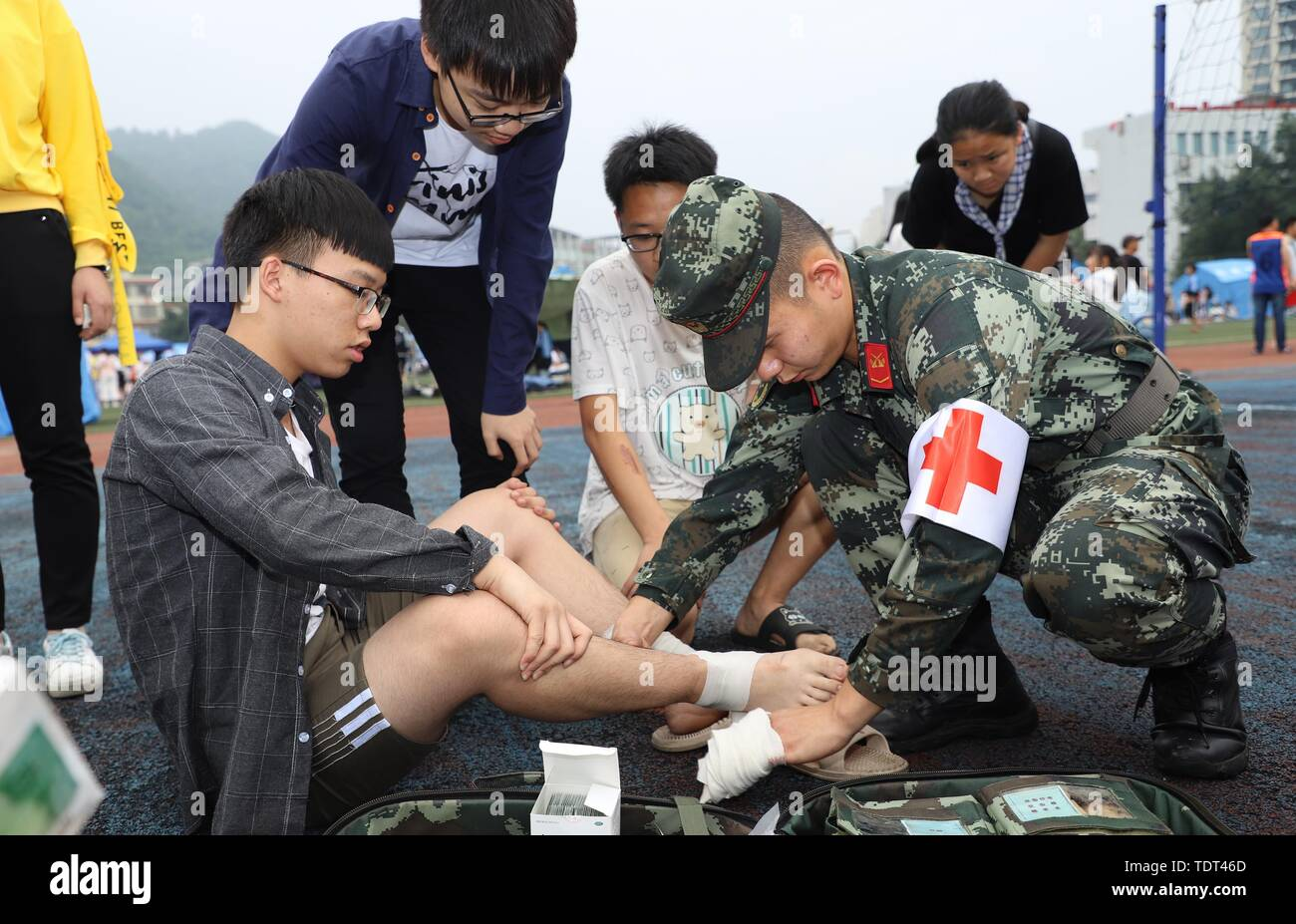 Changning, China's Sichuan Province. 18th June, 2019. A soldier binds up a student's ankle at a middle school in Gongxian County of Yibin City, southwest China's Sichuan Province, June 18, 2019. Thirteen people died and 199 were injured after a 6.0-magnitude earthquake hit southwest China's Sichuan Province at 10:55 p.m. Monday, the Ministry of Emergency Management said Tuesday. Credit: He Junwei/Xinhua/Alamy Live News - Stock Image