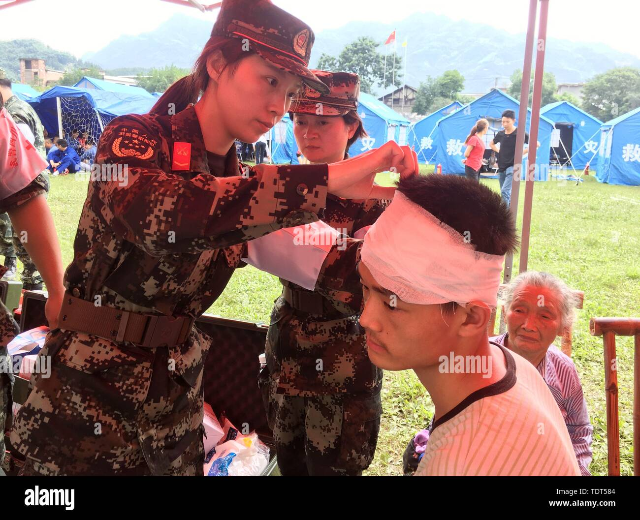 Yibin, China's Sichuan Province. 18th June, 2019. A medical staff member of armed police force treats an injured man at a temporary shelter in Shuanghe Town High School in Changning County of Yibin City, southwest China's Sichuan Province, June 18, 2019. Thirteen people died and 199 were injured after a 6.0-magnitude earthquake hit southwest China's Sichuan Province at 10:55 p.m. Monday, the Ministry of Emergency Management said Tuesday. Credit: Li Huashi/Xinhua/Alamy Live News - Stock Image