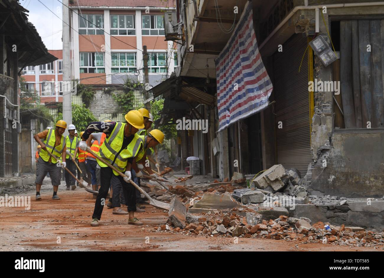 Changning, China's Sichuan Province. 18th June, 2019. Workers clean a road at Shuanghe Town in Changning County of Yibin City, southwest China's Sichuan Province, June 18, 2019. Thirteen people died and 199 were injured after a 6.0-magnitude earthquake hit southwest China's Sichuan Province at 10:55 p.m. Monday, the Ministry of Emergency Management said Tuesday. Credit: Liu Kun/Xinhua/Alamy Live News - Stock Image