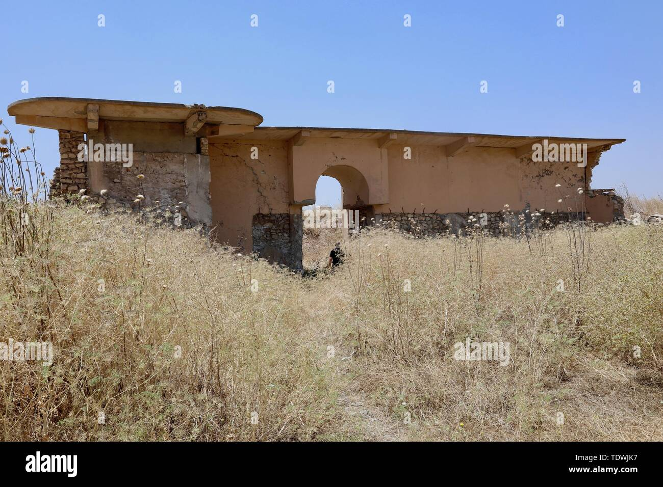 (190619) -- NIMRUD (IRAQ), June 19, 2019 (Xinhua) -- The photo taken on June 13, 2019 shows the destroyed gate of Ashurnasirpal Palace at archeological site of Nimrud, Iraq. Covered with thick layer of wild weeds, massive destruction of ancient palaces, temples and ziggurat left no signs for the Iraq's glorious archeological site of Nimrud after nearly three years of liberation from Islamic State (IS). (Xinhua) TO GO WITH Feature: Iraqi archaeological site lies in ruins after nearly 3 years of liberation from IS - Stock Image