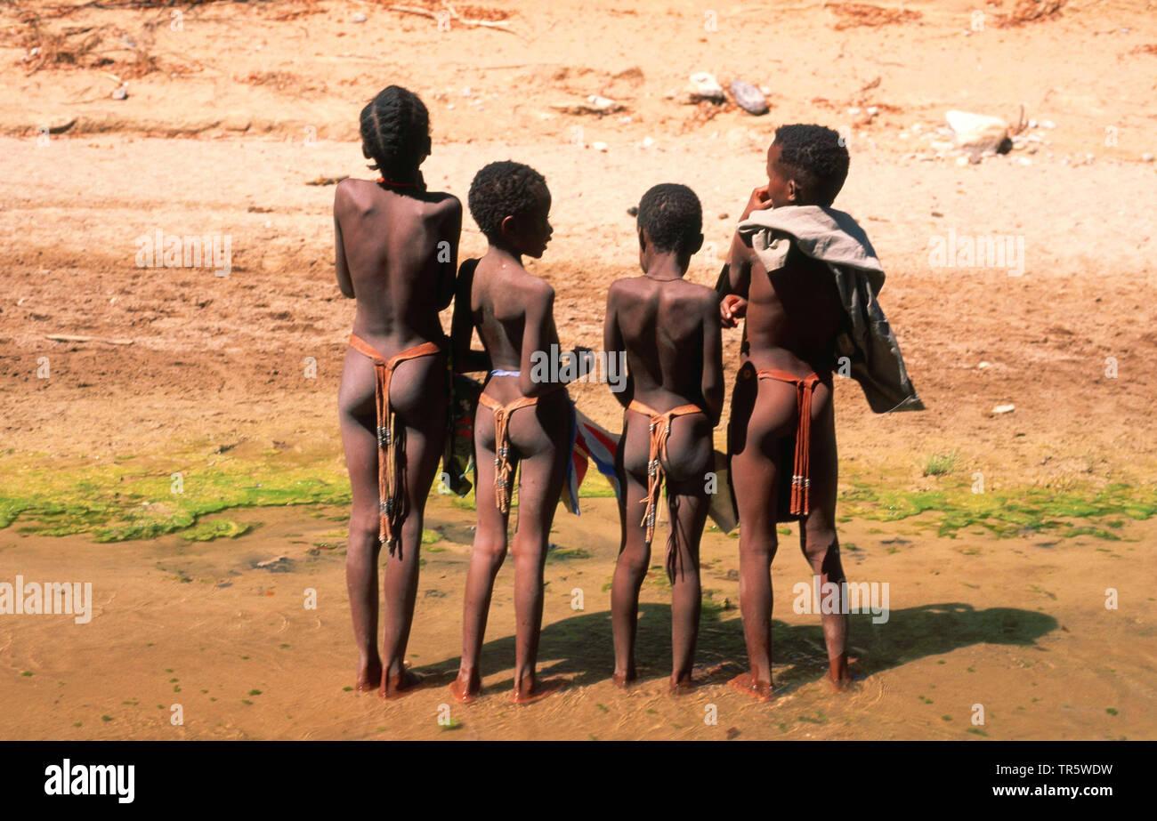 Damara-Kinder am Hoanib-Fluss, Rueckansicht, Namibia, Damaraland | Damara children at the Hoanib river, rear view, Namibia, Damaraland | BLWS466638.jp - Stock Image