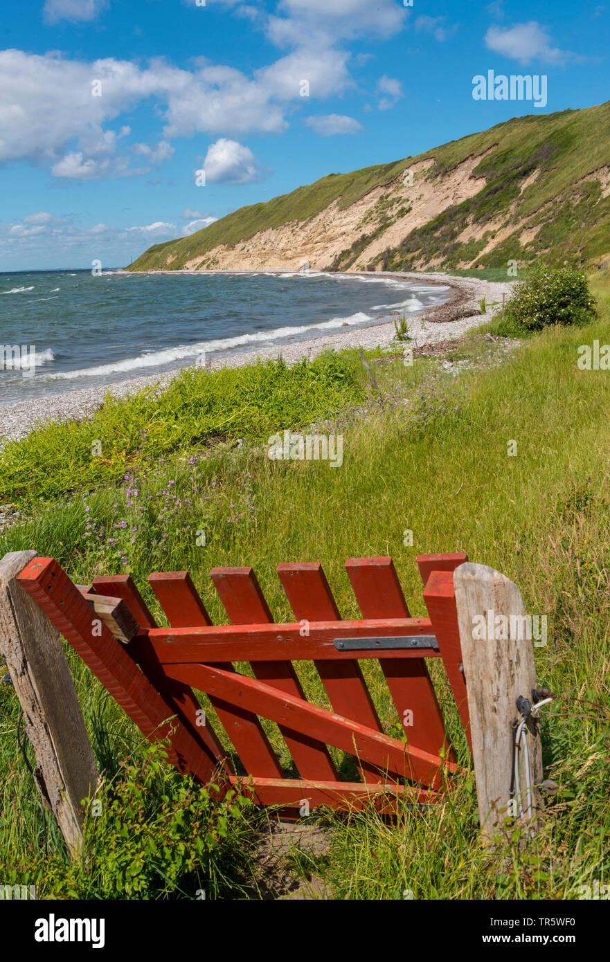 red pasture gate at the northeast coast of Samsoe Island in summer, Kattegat, Denmark, Samsoe, Maarup - Stock Image