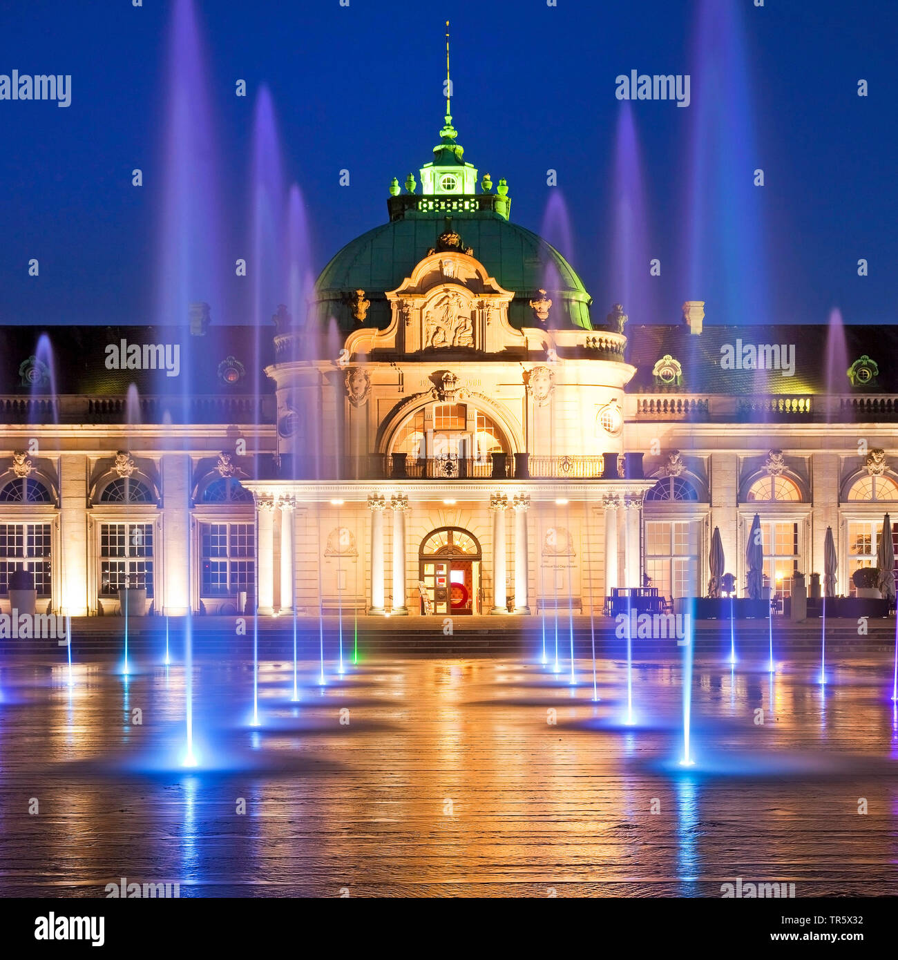 illuminated Kaiserpalais with mit water columns in the spa park at blue hour, Germany, North Rhine-Westphalia, East Westphalia, Bad Oeynhausen Stock Photo