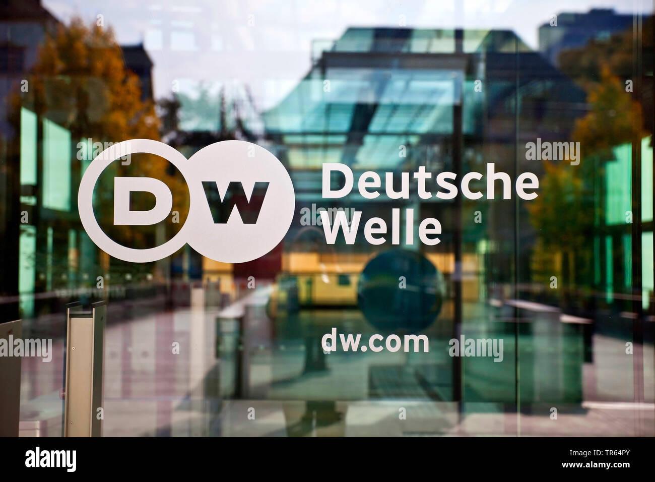 Logo Deutsche Welle an der Glastuer zum Hauptsitz des Rundfunksenders, Deutschland, Nordrhein-Westfalen, Bonn | logo of the German international broad - Stock Image