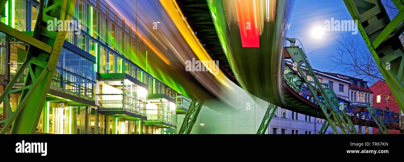 fahrende Schwebebahnen in der Daemmerung, Deutschland, Nordrhein-Westfalen, Bergisches Land, Wuppertal | moving Wuppertal cable railways in the evenin - Stock Image