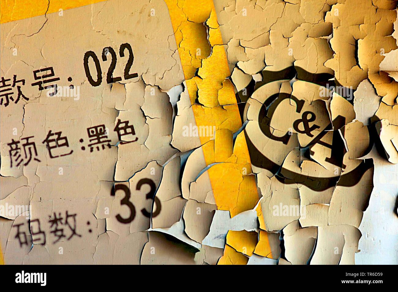 C & A Logo und chinesisches Etikett auf einer abblaetternden Wand, Traditionsunternehmen C&A prueft den Verkauf des Unternehmens nach China, Deutschla - Stock Image