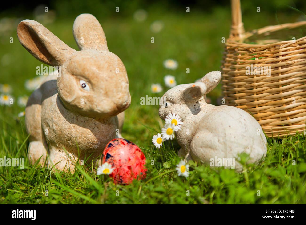 Deko-Osterhasen mit Ostereiauf dem Rasen, Deutschland | Easter bunnies and Easter egg on lawn, Germany | BLWS482610.jpg [ (c) blickwinkel/R. Schoenenb - Stock Image