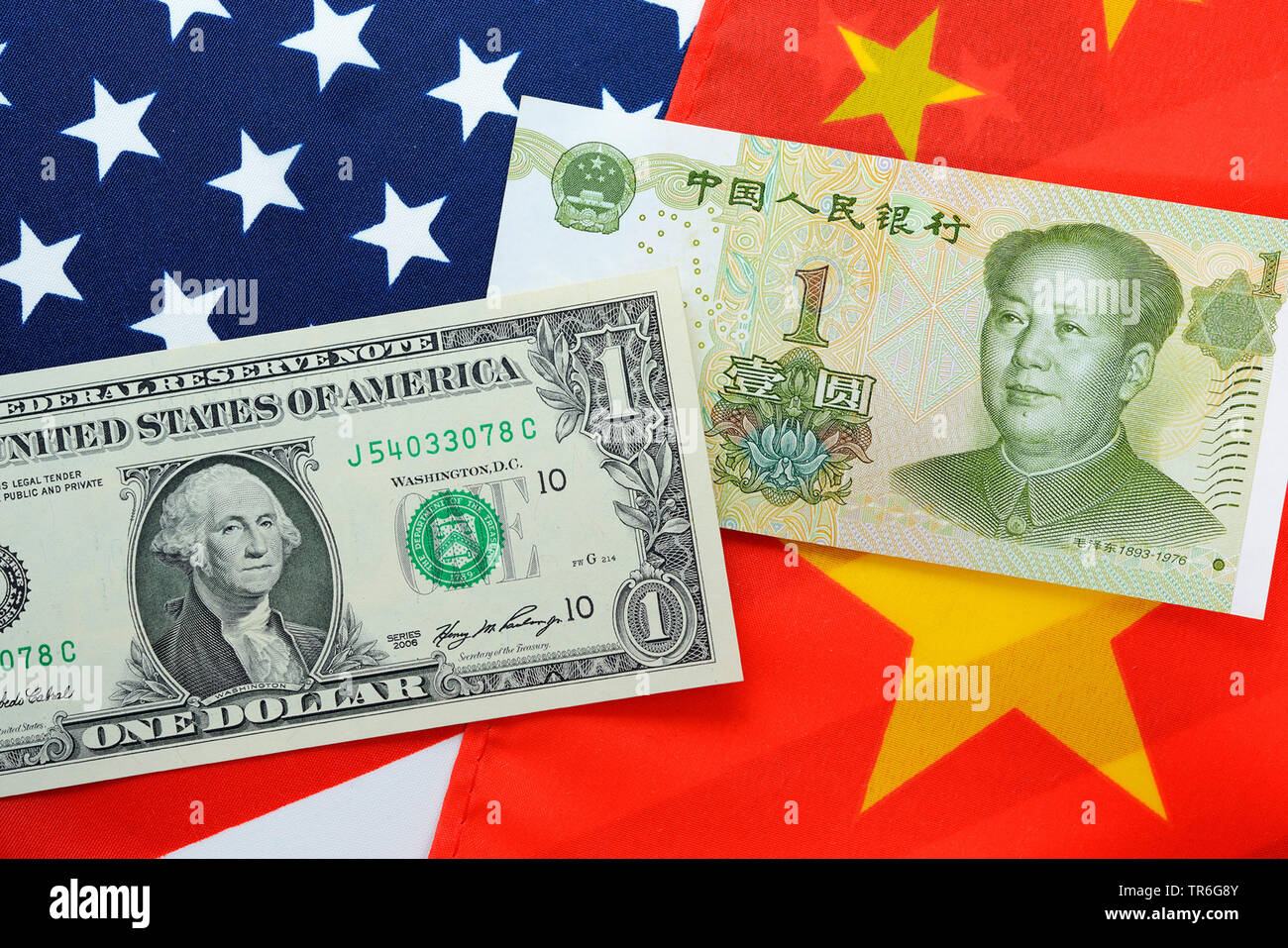 flaggs of USA and China with dollar and Yuan bills, threaten commercial war - Stock Image