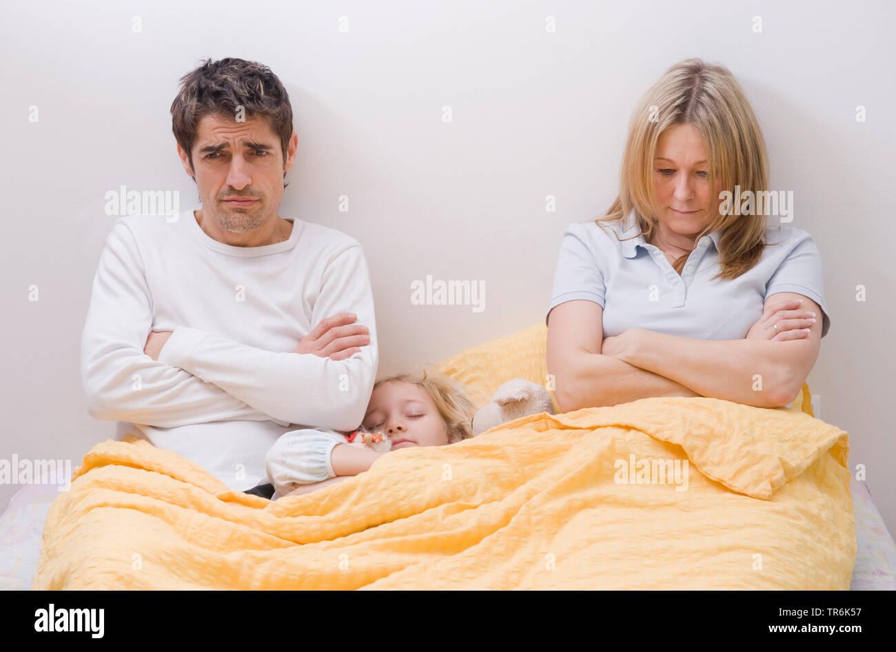 Tochter schlaeft zwischen den Eltern im Ehebett, Eltern sind genervt   daughter sleeping between parents in bed   BLWS485888.jpg [ (c) blickwinkel/McP - Stock Image