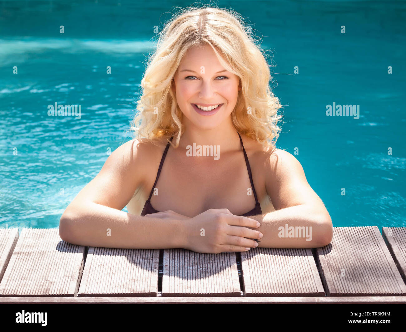 junge huebsche Blondine am Beckenrand eines Swimmingpools, Deutschland | young blond woman in a swimming pool, Germany | BLWS486389.jpg [ (c) blickwin - Stock Image
