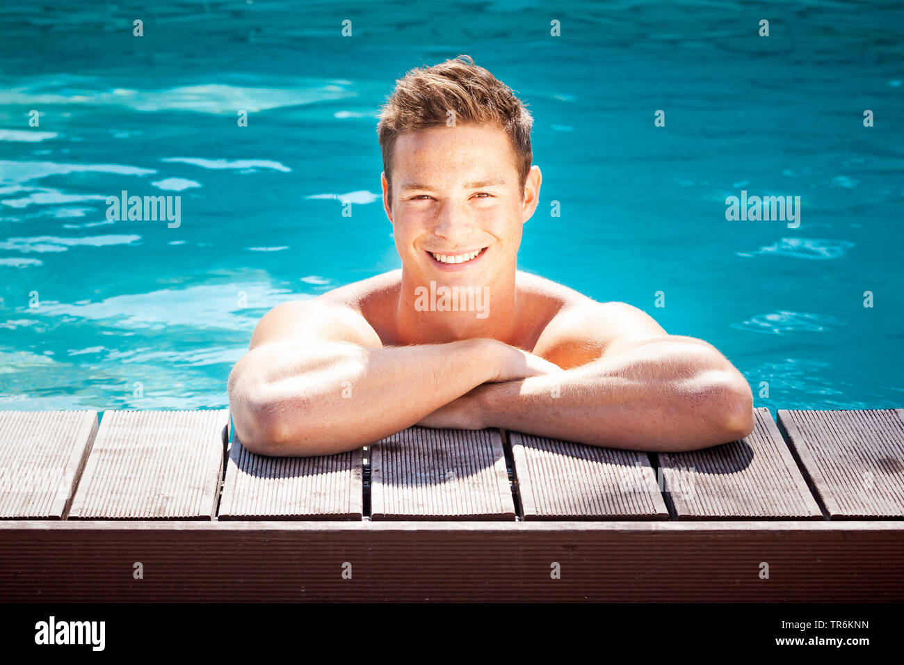 junger dunkelblonder Mann am Beckenrand eines Swimmingpools, Deutschland | young blond man in a swimming pool, Germany | BLWS486390.jpg [ (c) blickwin - Stock Image