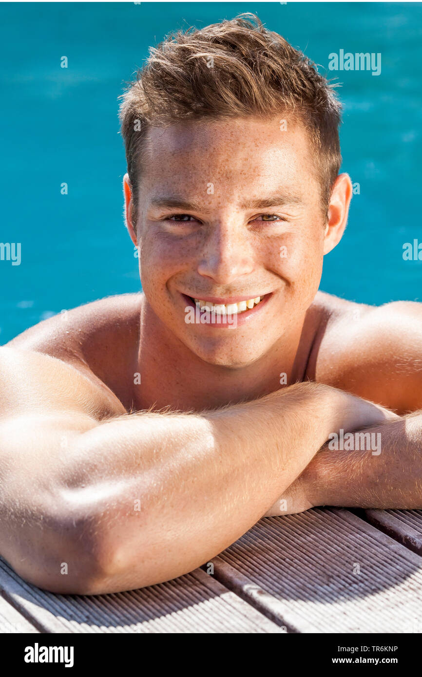 junger dunkelblonder Mann am Beckenrand eines Swimmingpools, Deutschland | young blond man in a swimming pool, Germany | BLWS486391.jpg [ (c) blickwin - Stock Image