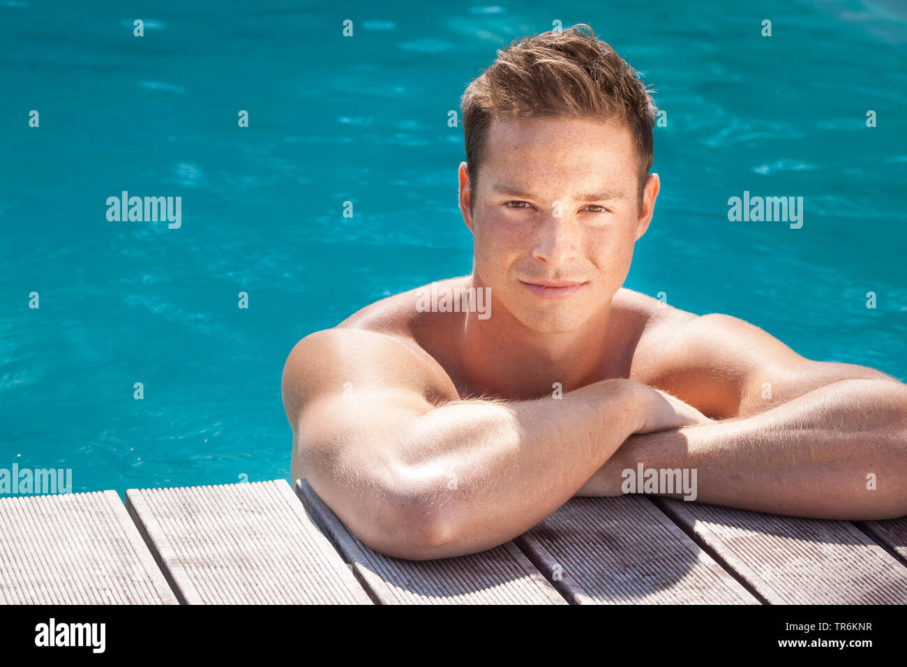 junger dunkelblonder Mann am Beckenrand eines Swimmingpools, Deutschland | young blond man in a swimming pool, Germany | BLWS486393.jpg [ (c) blickwin - Stock Image